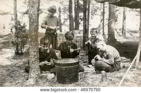 PLOCICZNO, POLAND, CIRCA 1957 - vintage photo of group of scouts peeling potatoes during a summer camp, Plociczno, Poland, circa 1957