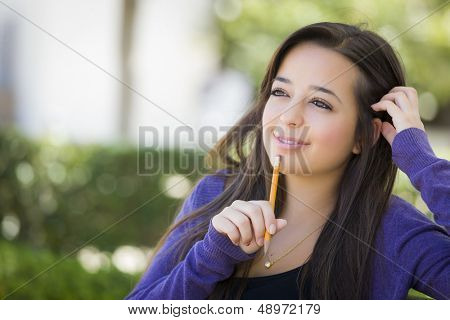 Attractive Pensive Mixed Race Female Student with Pencil Sitting on Campus Bench.