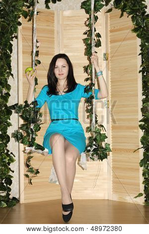 Happy Woman With Apple Sits On Swing Overgrown With Green Ivy.