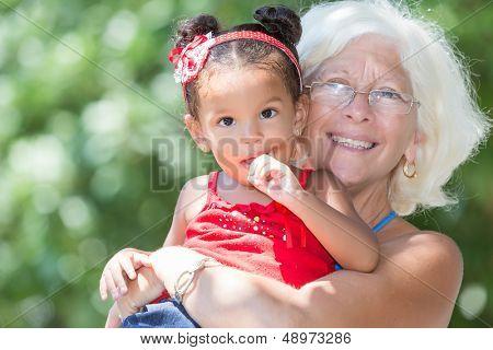 Avó caucasiana carregando sua pequena neta Latina