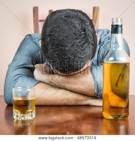 Drunk man sleeping with a whisky bottle and a glass  on his table