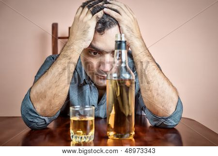 Drunk and depressed hispanic  man suffering a headache (with a liquor bottle on a table)