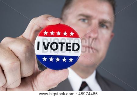 A man who voted holds up his voting badge lapel pin.