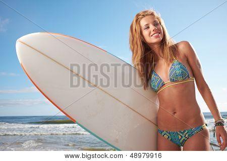 Hermosa joven surfista en Bikini con tabla de surf en la playa