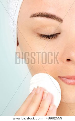 Woman removing makeup on blue background
