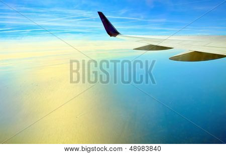 Wing of airplane flying over the ocean