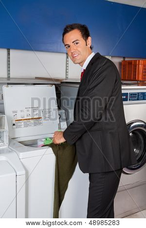 Portrait of handsome young businessman washing clothes at laundromat