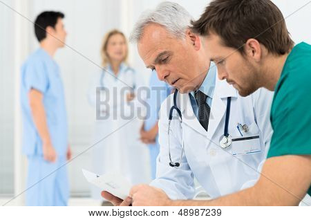 Group Of Doctors Involved In Serious Discussion With Medical Records