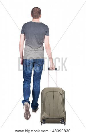 back view of walking  man  with suitcase.  brunette guy in motion. backside view of person.  Isolated over white background. young man goes to side of a rolling travel bag on wheels