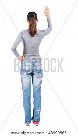 hintere Ansicht der Frau. Junge Frau in Jeans drückt etwas nach unten. Isolated over white Background.
