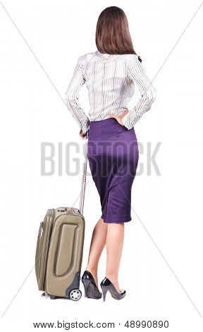 Back view of stylishly dressed brunette business woman with suitcase looking up. Standing young girl.   Isolated over white background. languid girl in heels looks into the distance