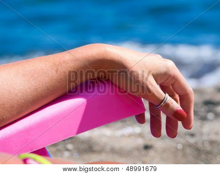 Woman Relaxes On A Deck Chair, Beach, Facing The Sea
