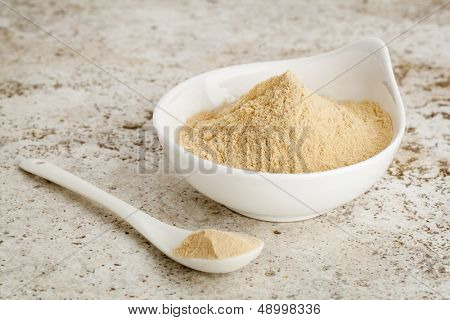 maca root powder - a small bowl with a spoon against ceramic tile surface