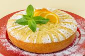 picture of testis  - Home made whole testy orange cake on red plate - JPG