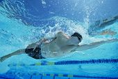 foto of watersports  - Low angle view of a young man swimming underwater - JPG