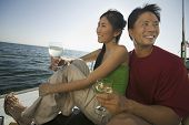 Smiling couple holding wine glasses on boat against the sea and sky