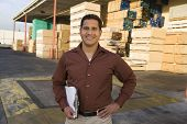 stock photo of baby delivery  - Portrait of a smiling confident supervisor with clipboard outside warehouse against stack of wood - JPG
