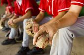 picture of mating  - Low section of baseball team mates sitting in dugout with player holding a ball in foreground - JPG