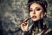 stock photo of smoking woman  - Portrait of a beautiful steampunk woman over grunge background - JPG