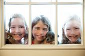 stock photo of raindrops  - three sister friends looking through the window with a pup and raindrops - JPG
