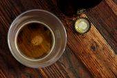 Top view of near empty beer glass with bottle cap and bottle on rustic wood background.  Low key sti