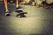 stock photo of skate  - Summer vintage skateboarder foot close and the street - JPG