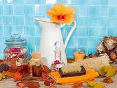 foto of bath sponge  - Exotic spa bathing accessories with an orange hibiscus flower in a jug against turquoise blue tiles with rose petal potpourri bath salts sponges and a variety of luxury bathing accessories - JPG