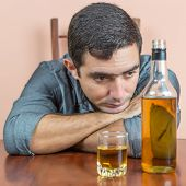 stock photo of liquor bottle  - Drunk and depressed hispanic  man with an alcoholic liquor bottle and a glass containing whisky or rum - JPG