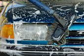 stock photo of car wash  - Foamy front of a blue car being cleaned - JPG