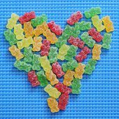 image of gummy bear  - gummy bears of different colors forming a heart on a blue woven background - JPG