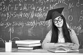 Black-and-white image of student in graduation hat and eyeglasses looking at camera on background of