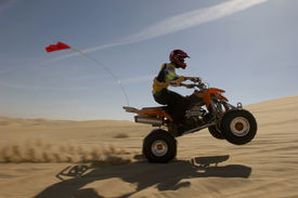 foto of four-wheelers  - Side view of a quad bike rider doing wheelie in desert against the sky - JPG