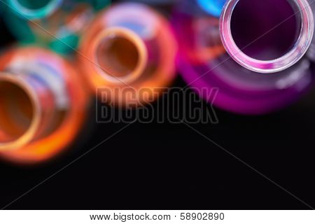 Image of several flasks with multi-color liquids, focus on one of them