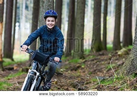 Girl biking on forest trails