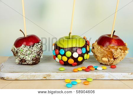 Candied apples on sticks on bright background