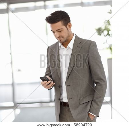 Young businessman standing at office building, using mobilephone.