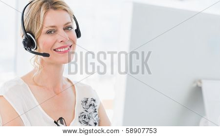 Portrait of a casual young woman with headset using computer in a bright office