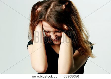 Portrait of a frustrated young screaming woman pulling her hair on gray background