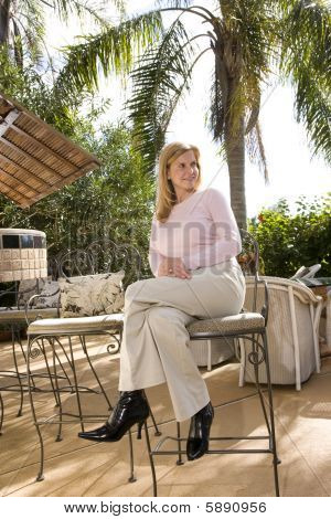 Mature woman on tropical vacation at a resort sitting outdoors