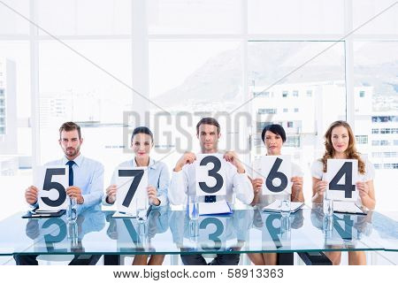 Portrait of a group of panel judges holding score signs in a bright office