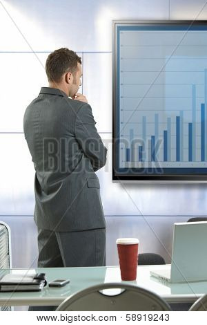 Young businessman doing presentation explaining diagram at meetingroom front of LCD display.