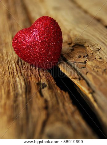 Red heart on a background of wood