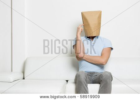 Inquiring anonymous man with head covered by a blank paper bag sitting on sofa with finger at temple, while thinking, empty space for text, on white background.