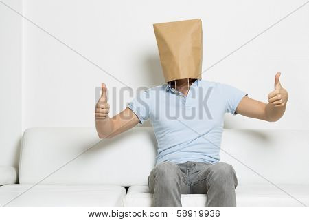 Thumbs up by anonymous man with head covered by a blank paper bag sitting on sofa, empty space for text, on white background.