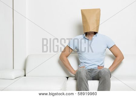 Serious anonymous man with head covered by a blank paper bag sitting on sofa with arms akimbo, empty space for text, on white background.