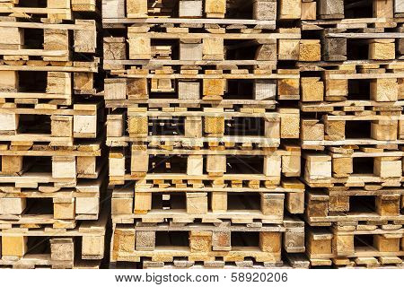 Wooden transport pallets in stacks.