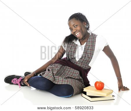 An attractive tween girl looking happy but a bit shy as she relaxes on the floor with 3 books and an apple.  On a white background.