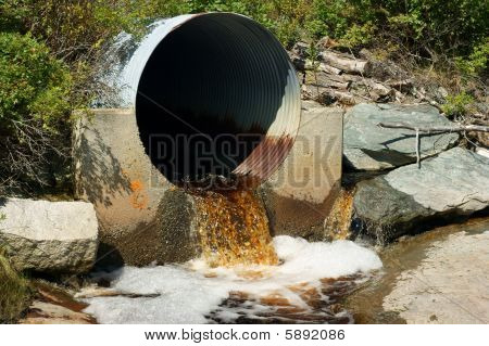 Brown runoff water from rusted culvert