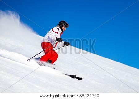 Male Skier Speeding Down Ski Slope