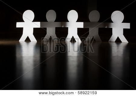 Paper people team group holding hands.